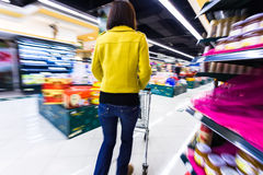 Young woman shopping in the supermarket,motion blur Stock Photo