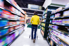 Young woman shopping in the supermarket,motion blur Stock Photos