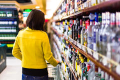 Young woman shopping in the supermarket,wine shelves Stock Photo