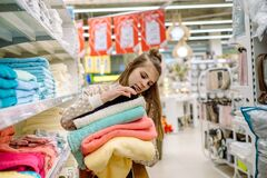 Young Woman Shopping Towels. A Teenager Picks A Big Towel On The Shelves Of A Store. Multi-colored Cotton Fluffy. Homeliness Royalty Free Stock Photos