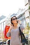 Young woman in shopping using a mobile phone Royalty Free Stock Photography