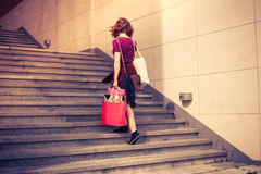 Young woman with shopping walking up stairs Royalty Free Stock Image