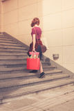 Young woman with shopping walking up stairs Stock Image