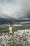 Young woman at the shore. Young woman in light dress feeling the wind on a beach on a stormy day Stock Photos