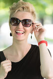 Young woman with short blond hair and sunglasses. Beautiful fashionable young woman with short blond hair and sunglasses posing in the park royalty free stock photos