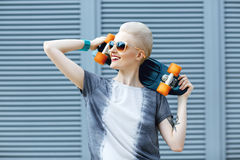 Young woman with short blonde hair smiling on the fashion background and holding little penny skateboard behind her head. And looking awawy . The girl in joyful Royalty Free Stock Photo