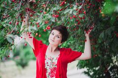 Young woman with short hair-cut standing near cherry tree Royalty Free Stock Image