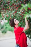 Young woman with short hair-cut standing near cherry tree Stock Photos