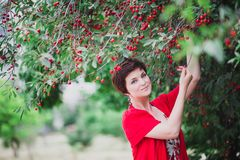 Young woman with short hair-cut standing near cherry tree. Beautiful young woman with short hair-cut and blue eyes standing near cherry tree Stock Images