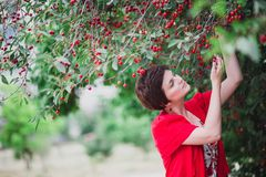 Young woman with short hair-cut standing near cherry tree Stock Photo