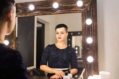 Young woman with short hair looking herself reflection in mirror Stock Photos