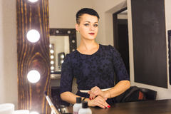 Young woman with short hair looking herself reflection in mirror Royalty Free Stock Images