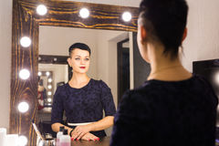 Young woman with short hair looking herself reflection in mirror. Young woman looking herself reflection in mirror Royalty Free Stock Photography