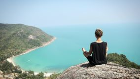 Young woman with short hair is sitting on the edge of the cliff with a view. Young woman with short hair is sitting on the edge of the cliff with a beautiful stock video footage