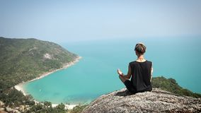 Young woman with short hair is sitting on the edge of the cliff with a view. Young woman with short hair is sitting on the edge of the cliff with a beautiful stock footage