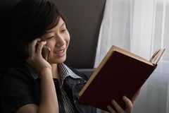 Woman use phone and reading book sit on the side of the window Royalty Free Stock Photos