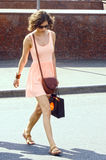 Young woman in a short pink dress summer, sunny day crossing the road near the restaurant Prague name Royalty Free Stock Image