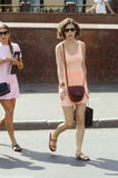Young woman in a short pink dress summer, sunny day crossing the road near the restaurant Prague name Sunglasses Stock Photos