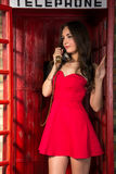 Young woman in a short red dress talking on the phone Stock Photo