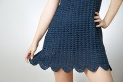 Young woman in a short skirt knitted on a gray background Royalty Free Stock Image