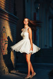 Young woman in a short white dress is danced in a dance on a deserted street on a wall background. She is dancing like crazy. Active girl wears a white dress Royalty Free Stock Image
