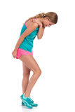 Young Woman With A Shoulder Injury. Young woman in pink shorts and turquoise shirt is standing and holding her shoulder. Side view. Full length studio shot royalty free stock photos