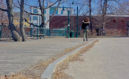 Young girl with curly red hair walking a board walk in early spring. Young woman with shoulder length, tight red curls walks along a wooden walkway in fall Stock Photos