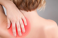 Young woman with shoulder pain, massaging her shoulder. Young woman feeling exhausted and pain in shoulder stock image
