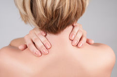 Young woman with shoulder pain, massaging her shoulder. Young woman feeling exhausted and pain in shoulder royalty free stock photo