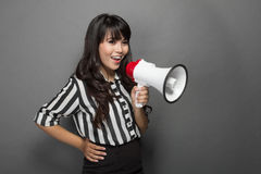 Young woman shouting with a megaphone against grey background Stock Photos
