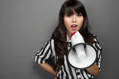 Young woman shouting with a megaphone against grey background. Portrait of a young woman shouting with a megaphone against grey background Stock Photo