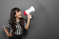 Young woman shouting with a megaphone against grey background. Portrait of a young woman shouting with a megaphone against grey background Royalty Free Stock Photography