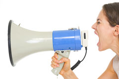 Young woman shouting through megaphone Royalty Free Stock Images