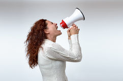 Young woman shouting into a megaphone. Side view on white conceptual of a rally or protest Royalty Free Stock Image