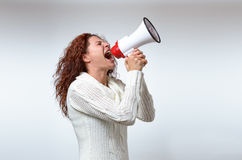 Young woman shouting into a megaphone. Side view on white conceptual of a rally or protest Stock Photo