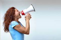 Young woman shouting into a megaphone. Side view on white conceptual of a rally or protest Stock Photography