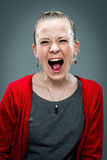 Young Woman Shouting. Over a Grey Background Royalty Free Stock Photos