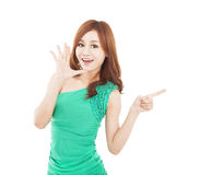 Young woman shouting and pointing at something. Happy asian  young woman shouting and pointing at something Royalty Free Stock Image
