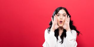 Young woman shouting on a solid background Stock Image