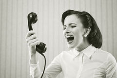 Woman shouting into telephone Stock Photo