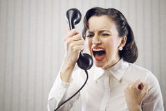 Young Woman shouting into telephone Royalty Free Stock Photography