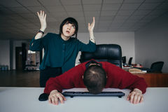 Young Woman shouting to his colleague and active gestures, the man lowered his head in disappointment keyboard. royalty free stock photography