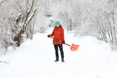 Young woman shoveling rural road Stock Images