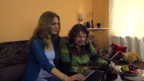Young woman show her grandma how use computer. Two generation stock footage