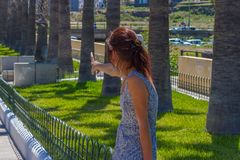 Young woman show something by finger in the park. View from behind and back. Young woman show something by finger in the park. View from behind royalty free stock images
