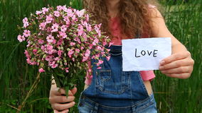 Young woman show word Love and pink flowers stock video
