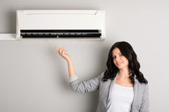 Young woman showing air conditioner Stock Photo