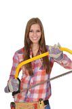 Young woman showing a big saw. Attractive young woman with long hair holding a large saw Royalty Free Stock Images