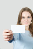 Young woman showing blank business card. Young Woman showing a business card in her hands Stock Image