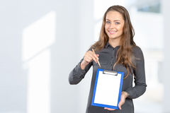 Young woman showing blank clipboard Stock Image